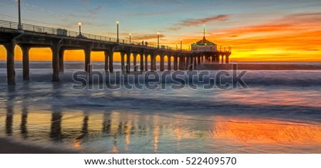 sun setting over manhattan beach pier,as powerful waves roll in,and a very colorful sky is reflected on the beach. manhattan beach,California #522409570