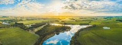 Sun setting over scenic Australian countryside grasslands and pastures with river passing through - aerial panorama