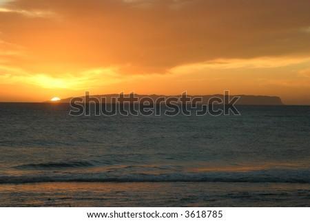 Sun setting over the island of Ni'ihau, Hawaii.