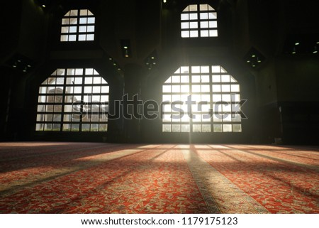Sun shine cut through large window in  masjid fatimah makkah al mukarammah falls in the surface of the red carpets with flora pattern make this place preoccupied for prayer #1179175123