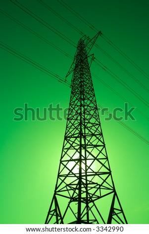 Sun shining behind an electricity pylon. Green energy.