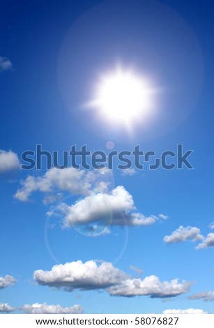 Sun shining in blue sky with some clouds
