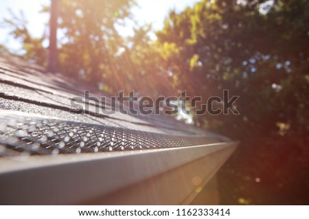 Sun shining on mesh plastic guard in the gutter on a roof