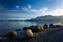 Sun shining on stones on a rocky beach on Lake Tahoe with views of the Sierra Nevada Mountains in California.
