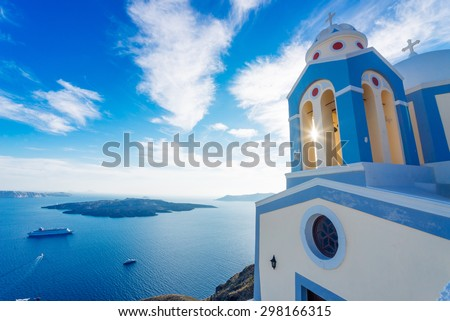 Sun shining through belltower of a church with a view of Santorini volcanic caldera and ships in it, Santorini, Cyclades, Greece #298166315