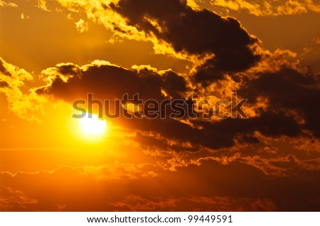 sun shining through clouds at sunset