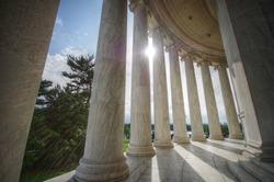 Sun shining through columns at the Jefferson Memorial in Washington DC
