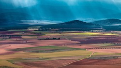 Sun shining through heavy stormclouds on dirt road through colorful spanish agricultural farmland