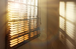 Sun shining through window blinds in room