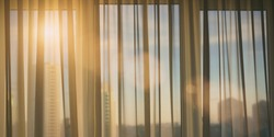 sun shining through window curtain from city street cityscape background