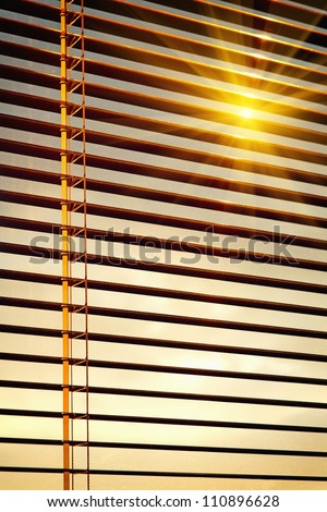 Sun shining through yellow horizontal jalousie out of wood
