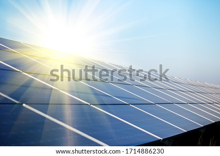 Sun shining to the solar panels at power station. Solar pawer station at sunset time. Foto stock ©
