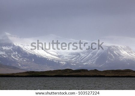 Sun shining trough clouds on snowcapped mountains, Iceland