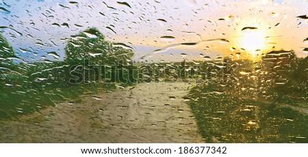 Sun shower. Drops of rain on windscreen against sunset
