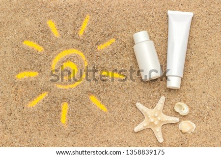 Sun sign drawn on sand, starfish and white tube, bottle of sunscreen. Template mockup for your design. Creative top view.