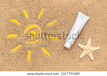 Sun sign drawn on sand, starfish and white tube of sunscreen. Template mockup for your design. Creative top view.