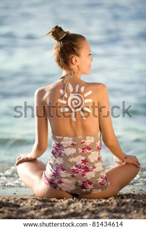 Sun symbol written in sunlotion on womans back on beach