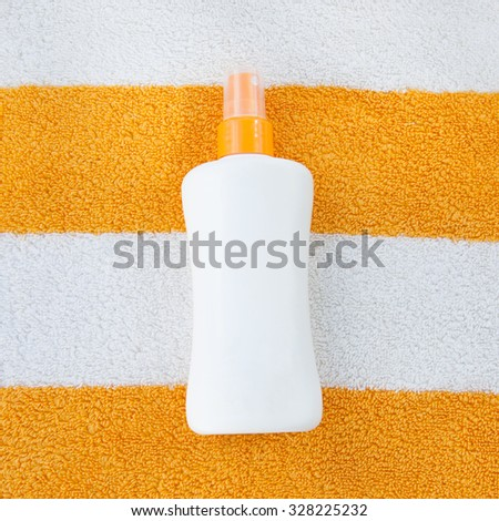 Sun tan spray lotion in white bottle lying on the white and orange striped beach towel background.