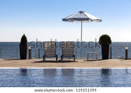 Sun umbrella and relaxing chairs near a pool