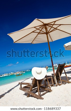 Sun umbrella with Sun Hat on chair longue - stock photo