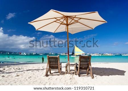 Sun umbrella with Sun Hat on chair longue  on tropical beach