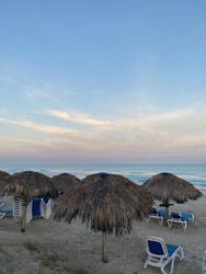 Sun umbrellas from palm leaves and sun loungers on the shore of the Atlantic Ocean at the Star Fish Hotel in Varadero