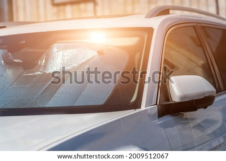 Sun visor or sun reflector on car windshield protects car in parking lot. There is light from sun shining on windshield Stock fotó ©