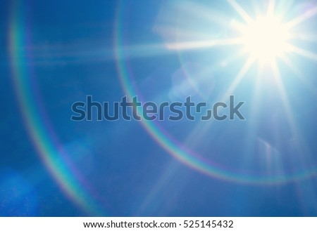 Sun with lens flare, on blue sky background. #525145432