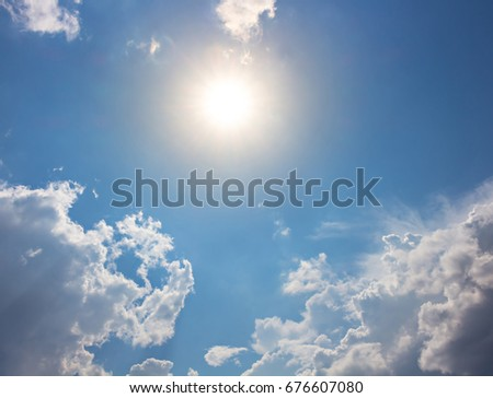 Sun with orange light on blue sky and bright clouds #676607080