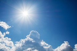 Sun with rays on a background of blue sky with clouds