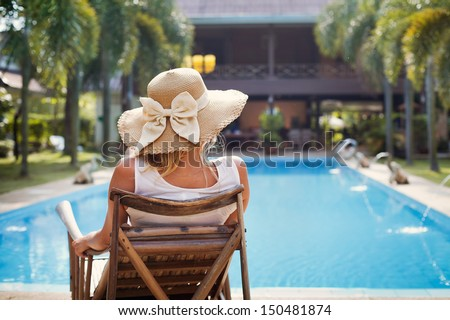 sunbath near swimming pool, fashion woman in hat