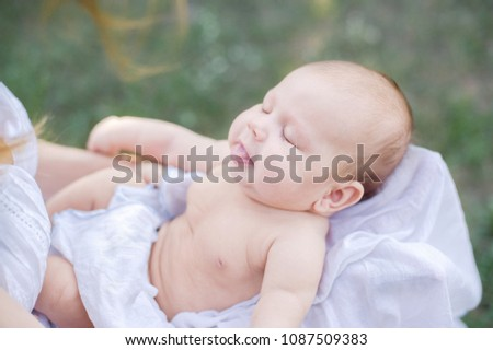 sunbathing baby. Child Taking a Sunbath. Morning sunshine good for the health of a newborn. lack of vitamin D for children under one year #1087509383