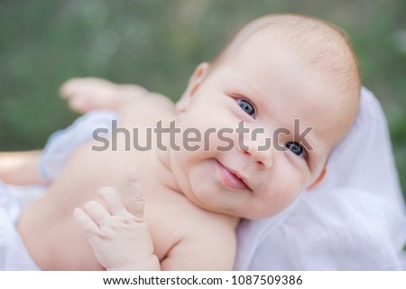sunbathing baby. Child Taking a Sunbath. Morning sunshine good for the health of a newborn. lack of vitamin D for children under one year #1087509386