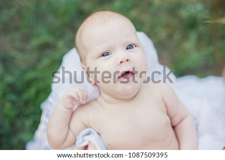 sunbathing baby. Child Taking a Sunbath. Morning sunshine good for the health of a newborn. lack of vitamin D for children under one year #1087509395