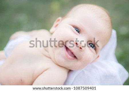 sunbathing baby. Child Taking a Sunbath. Morning sunshine good for the health of a newborn. lack of vitamin D for children under one year #1087509401
