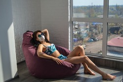 Sunbathing on the balcony. Vacation 2020. During quarantine due to the coronavirus, the girl in protective mask stays at home and sunbathes on the balcony. Pretty young woman sunbathing on the balcony