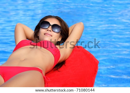 Sunbathing woman by pool on summer holidays. Natural beautiful multiracial Asian Caucasian young female model in bikini