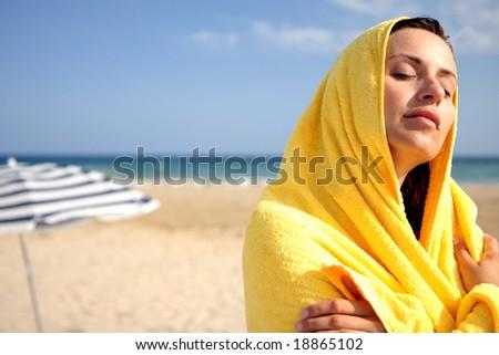 sunbathing woman in yellow towel with coastline in background