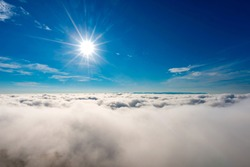 Sunbeam above the fog and clouds in the blue sky.Photography with Lense flare effect.