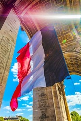 Sunbeam Sun Rays Arc de Triomphe French Flag Paris France. Completed in 1836 monument to the dead in the French Revolution and Napoleonic Wars. Includes tomb to unknown soldier