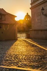 Sunbeams at dawn falling on the street in Prague