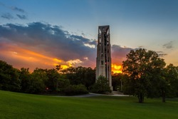 Sunbeams bursting through clouds at sunset behind the Carillon bell tower in Naperville, Illlinois just west of Chicago