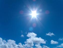 Sunbeams shining from sun in blue sky
