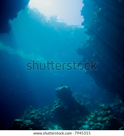 sunbeams shining through a hole in the roof of an underwater cave.