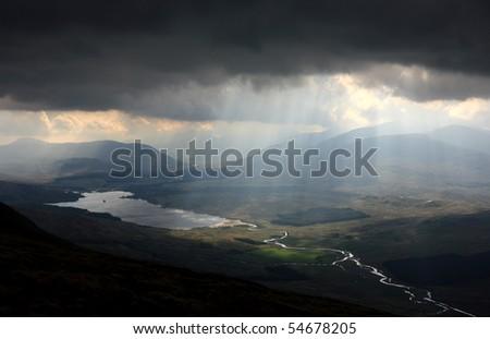 Sunbeams shining through dark clouds above Loch Tulla, Scotland