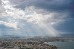 Sunbeams shining through the dramatic clouds over the city Chania. Greece. Crete.