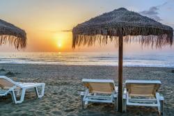 sunbed and umbrella on the sunset background, Torremolinos, Spain