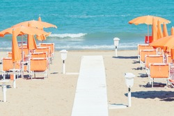 Sunbeds and parasols on the seashore. Beach, sea and umbrellas on summer day. Adriatic coast, Rimini, Italy, view from Gabicce Mare.