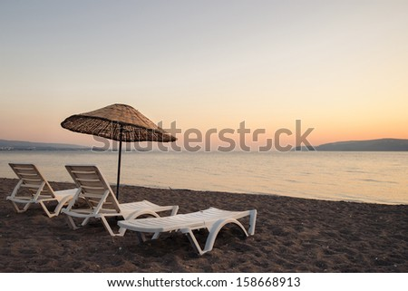 Sunbeds and umbrella by the sunset beach