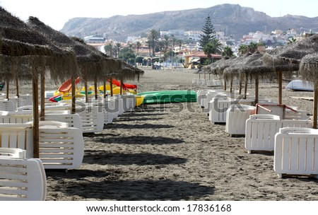 Sunbeds and wicker parasols on a Spanish beach